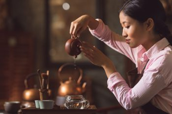 Young woman pouring tea from a teapot